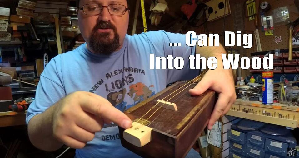 Shane Speal points to strings installed in the tail-end of a cigar box guitar neck