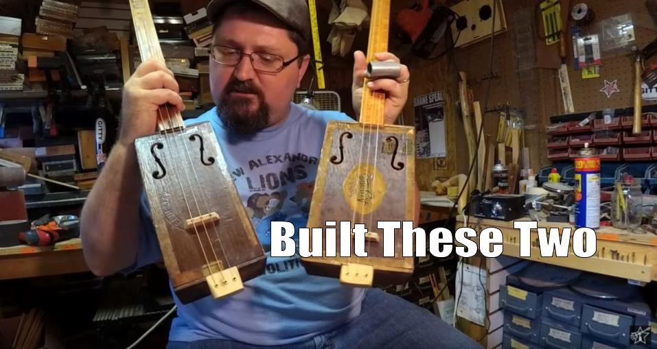 Shane Speal displays two guitars he built using antique cigar boxes