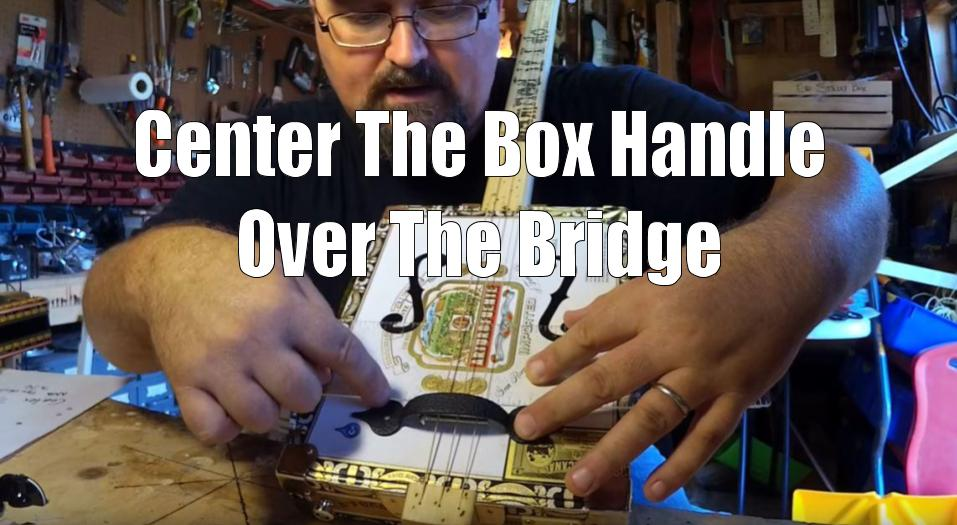Shane Speal centers a box handle over a cigar box guitar bridge
