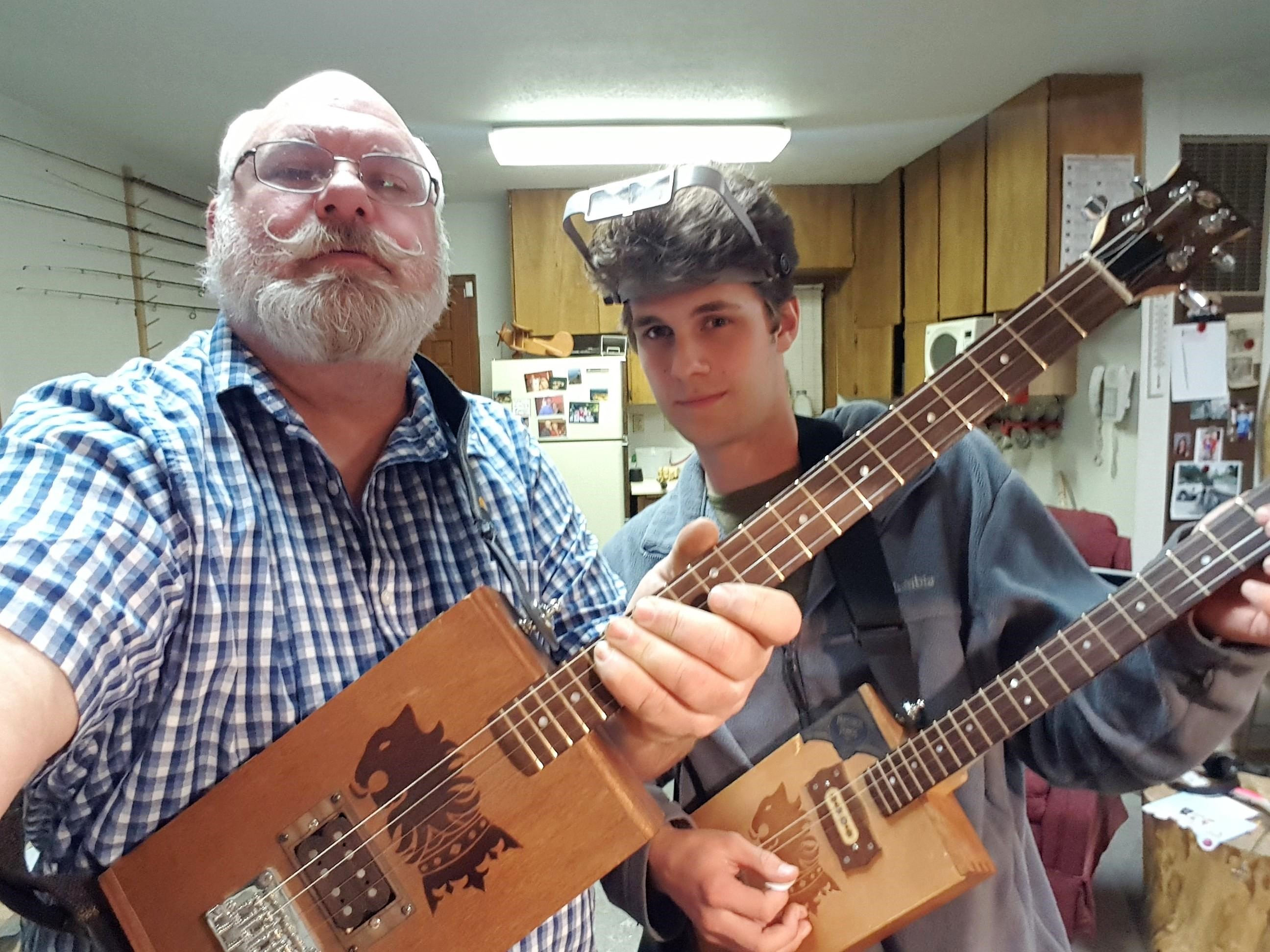 Roy B. and student holding cigar box guitars