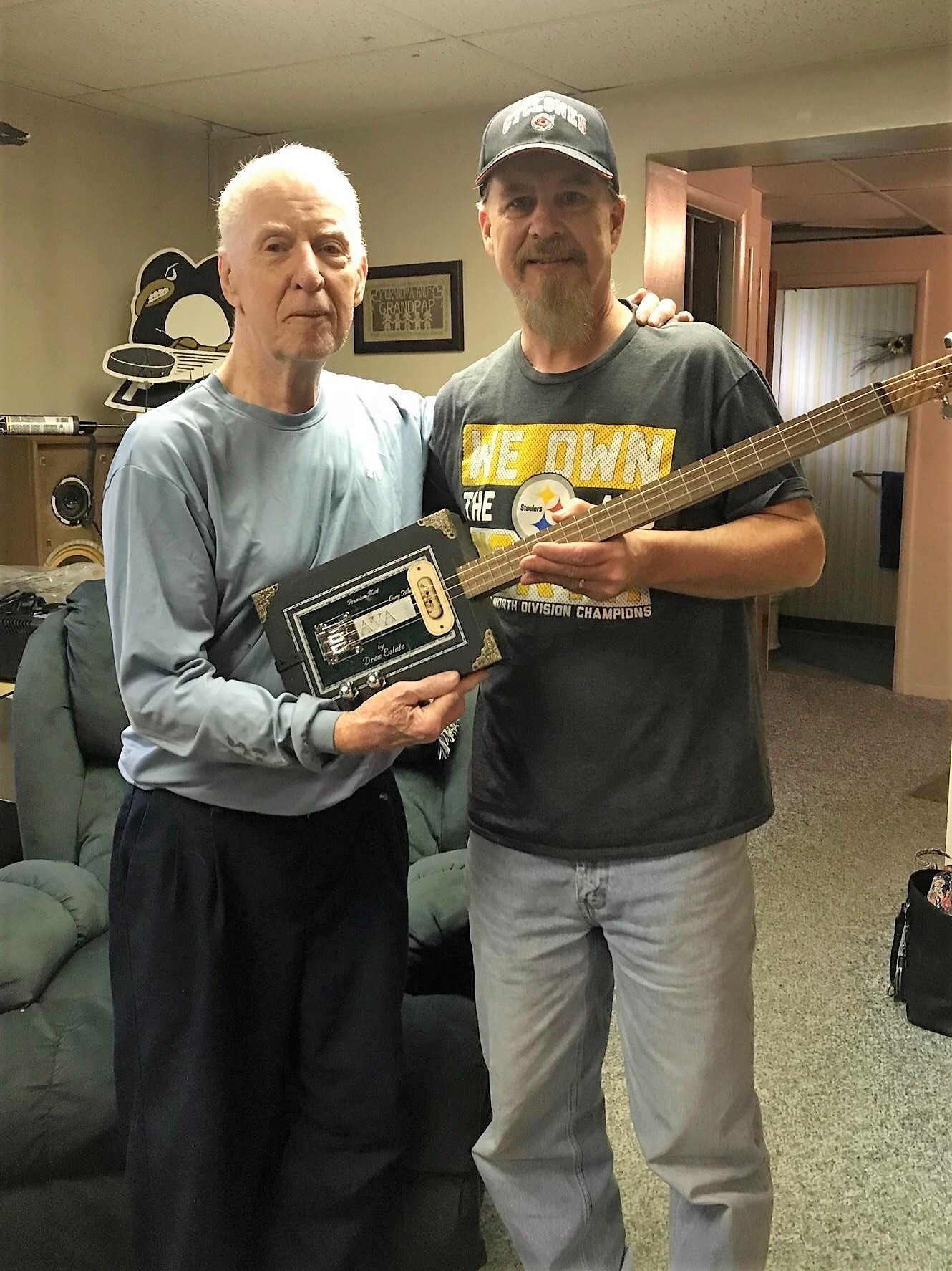 Scott M. and his dad holding the first cigar box guitar they've built together
