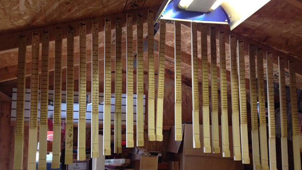 A batch of cigar box guitar necks hanging in Shane Speal's workshop