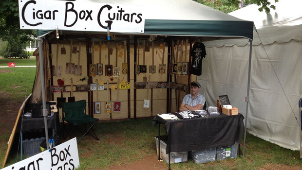 Shane Speal's cigar box guitar vending tent at a festival
