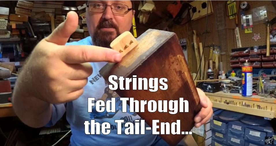 Shane Speal points to strings fed through the bottom of a cigar box guitar neck