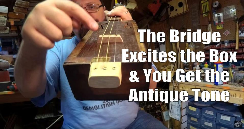 Shane Speal points to a hardwood bridge on a antique-cigar box guitar
